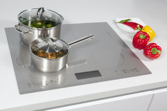 In the kitchen. Grey glass induction hob in the kitchen royalty free stock photos