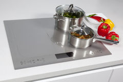 In the kitchen. Grey glass induction hob in the kitchen stock image