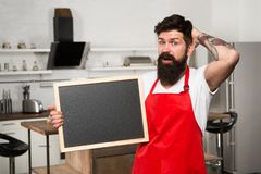 Kitchen hacks concept. Clever ways to organize kitchen. Cook hold blank chalkboard copy space. Secret tips. Useful. Information. Man bearded hipster red apron royalty free stock photo