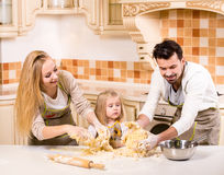 Kitchen. Happy parents and their young daughter are cooking, baking cakes in home kitchen stock photography