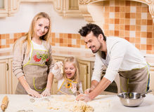 Kitchen. Happy parents and their young daughter are cooking, baking cakes in home kitchen royalty free stock photography