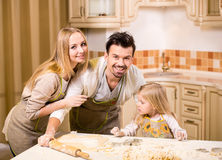 Kitchen. Happy parents and their young daughter are cooking, baking cakes in home kitchen royalty free stock photo