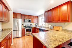 Kitchen with hardwood floor, stained cabinets, stainless steal fridge, and marble counters. Stock Photography