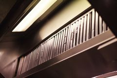 Kitchen hood exhaust hood, range hood, device containing mechanical fan hanging above stove in kitchen. It removes airborne. Grease, fumes, smoke, heat and royalty free stock photos