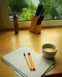 Kitchen inspiration. A white notepad with 3 pens on top. A white coffee mug next to it. Knife block and window in the background Royalty Free Stock Photo