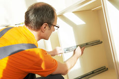 Kitchen installer at carpenter work Stock Image
