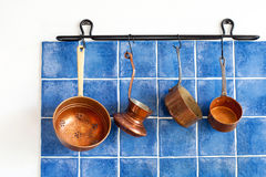 Kitchen interior, accessories. Hanging copper. Kitchen cuprum utensils hanging on blue tiled wall Stock Image