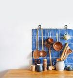 Kitchen interior, accessories. Hanging copper kitchenware set. Spoon, skimmer, colander. Blue tiles ceramic background. Stock Photography