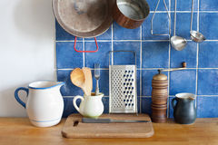 Kitchen interior accessories. pots jug pan cutting board, wooden spoon, cooper ladle stewpan. Royalty Free Stock Image