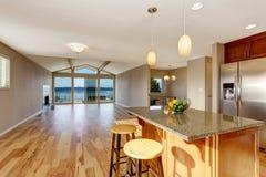 Kitchen interior with bar, stainless steel fridge, hardwood floor in luxury house. Stock Photo