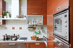 Kitchen interior with build in microwave oven. Part of Kitchen interior with wooden furniture and build in microwave oven Royalty Free Stock Photography