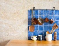 Kitchen interior. Hanging retro design copper kitchenware set. Pots, stewpots, coffee maker, spoon, skimmer. Kitchenware set.  Blue tiles, aged sand wall Stock Images