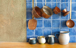 Kitchen interior. Hanging retro design copper kitchenware set. Pots, stewpots, coffee maker, spoon, skimmer. Kitchen design. Different sizes, colors pitchers on Stock Photos