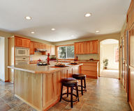 Kitchen interior with honey cabinets and built-in appliances. Kitchen interior with honey cabinets , built-in appliances and large kitchen island. Northwest, USA Royalty Free Stock Photos
