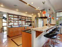 Kitchen interior with long wooden cabinets and shelves. Bar stand with modern leather stools. Northwest, USA Stock Image