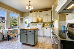 Kitchen interior in old house with island and antique table Stock Photography
