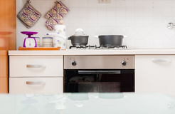 Kitchen interior with saucepans on the hob. Kitchen interior with saucepans on the gas hob, a built in oven and with kitchen utensils and equipment on the Stock Photos