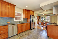 Kitchen interior with tile flooring and brown cabinets. Kitchen interior with tile flooring and modern brown cabinets, mosaic green backsplash and stainless Stock Photography