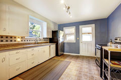 Kitchen interior with white cabinets and bright navy walls. Kitchen interior with white cabinets, tile floor and bright navy walls Stock Photography