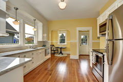 Kitchen interior with white cabinets, yellow walls and wood floor. Kitchen interior with white cabinets, stainless steel appliances, yellow walls and hardwood Royalty Free Stock Photography