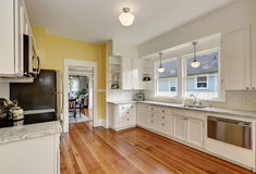 Kitchen interior with white cabinets, yellow walls and wood floor. Kitchen interior with white cabinets, stainless steel appliances, yellow walls and hardwood Stock Image