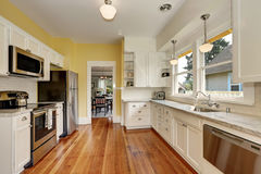 Kitchen interior with white cabinets, yellow walls and wood floor. Kitchen interior with white cabinets, stainless steel appliances, yellow walls and hardwood Stock Photography