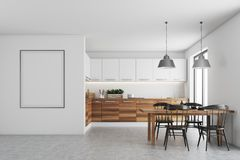 White dining room, poster, wood countertops. Kitchen interior with white walls, a concrete floor, wooden countertops, a table and chairs. A framed poster on the Stock Photo