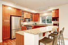 Kitchen interior. Wooden cabinets, granite tops and window view. Apartment Kitchen interior. Wooden cabinets, granite tops and window view. Also bar stools Stock Photo