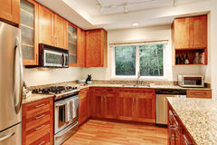 Kitchen interior. Wooden cabinets, granite tops and window view. Apartment Kitchen interior. Wooden cabinets, granite tops and window view. Northwest, USA Royalty Free Stock Image