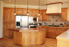 Kitchen with Island. A tidy kitchen built with pine and high-end appliances Stock Photos