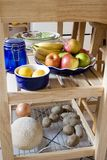 Kitchen Island with fruits, lemon, potatos, onion on the shelf Stock Photo