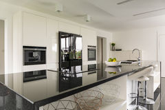 Kitchen island in luxurious interior. Kitchen island with marble wotktop in luxurious interior stock image