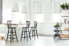Kitchen island under window. White lamps above kitchen island under a window with black bar stools in bright room with plants royalty free stock photos