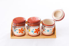 Kitchen jars on a wood shelf. Three kitchen jars with flower drawings are placed on a wood shelf - isolated on white stock photography