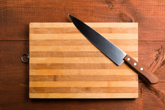 Kitchen knife and cutting board. On the wooden table Royalty Free Stock Image