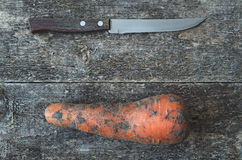 Kitchen knife and dirty carrot. Kitchen knife and organic dirty carrot whole on the wooden rustic background, top view. Knife and Carrot Background. Vegetable Royalty Free Stock Photo