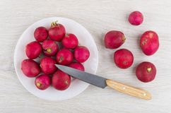 Kitchen knife, fresh radishes in plate, and lying on table. Kitchen knife, fresh radishes in white plate, and lying on wooden table. Top view Stock Images
