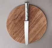 Kitchen knife lying on an old cutting board Stock Photography