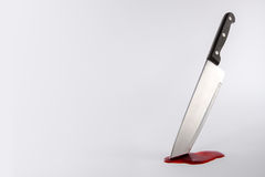 Kitchen knife in pool of blood with copy space. Kitchen knife stuck in surface with blood and copy space Stock Photo