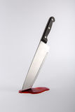 Kitchen knife in pool of blood. Kitchen knife stuck in surface with pool of blood Royalty Free Stock Photography