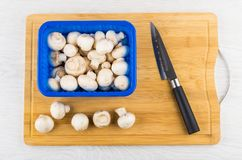Knife, raw mushrooms in container and on bamboo cutting board. Kitchen knife, raw mushrooms in container and on bamboo cutting board on wooden table. Top view Stock Photo