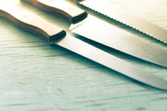 Kitchen knives sat on a wooden background Royalty Free Stock Photo