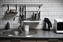 Kitchen in a loft style with concrete and brick walls and tiles, a sink, microwave, teapot and a modern lamp. Kitchen in a loft style with concrete and brick royalty free stock photo