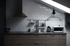 Kitchen in a loft style with concrete and brick walls and tiles, a sink, vent, microwave, teapot and a modern lamp. Kitchen in a loft style with concrete and royalty free stock images