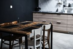 Kitchen in a loft style with concrete and brick walls and tiles. There is a black kitchen table with white chairs.  stock photo