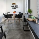 Kitchen with long, granite countertop. Concrete floor tiles and round table and chairs royalty free stock photo