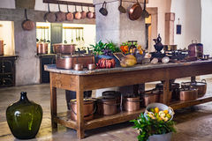 Kitchen of medieval castle copper pans and pots on wall and kitchenware cooking utensils table Royalty Free Stock Photo