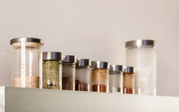 Kitchen metal shelf and glass jars with various spices Stock Photo