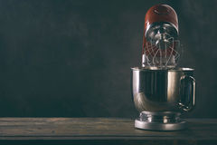 Kitchen mixer standing on wooden countertop Royalty Free Stock Photography