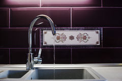 Kitchen mixer tap into granite work with running water Stock Images